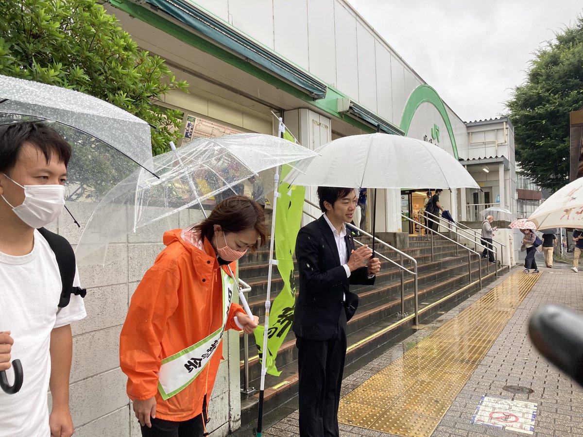 駅前で頭を下げる女性と男性